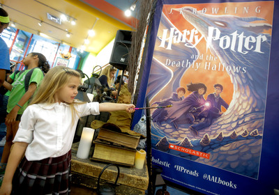 Wand in hand, a young fan celebrates Harry Potter at The Scholastic Store at the 2013 unveiling of the new cover of Harry Potter and the Deathly Hallows by illustrator Kazu Kibuishi.