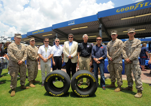 "(L to R) Members of the U.S. military, Joie Chitwood, President of Daytona International Speedway, Greg Stucker, Director of Goodyear Racing, Mike Helton, President of NASCAR, Martin C. Boire, chairman of Support Our Troops and Greg Biffle, NASCAR driver celebrate the launch of the ""Goodyear Gives Back"" campaign at Daytona International Speedway on Thursday, July 5, 2012. Goodyear is transforming the appearance of all related racing tires over the July 4th holiday race weekend, replacing the traditional sidewalls with a symbolic yellow  ..."