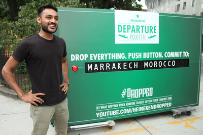 "Drew Nagda at the Heineken Departure Roulette on September 12, 2013 in New York. The social experiment challenged travelers to leave right away to unknown destinations. Drew tweeted to @Heineken_US ""I will drop everything (including this sandwich) & travel! 'my bags are packed, & I'm ready to go..' #dropped #jetplane,"" and Heineken surprised Drew at work, with a sandwich of course, to put his words to the test. Without hesitation, he dropped the sandwich to play Departure Roulette.  (PRNewsFoto/Heineken)"