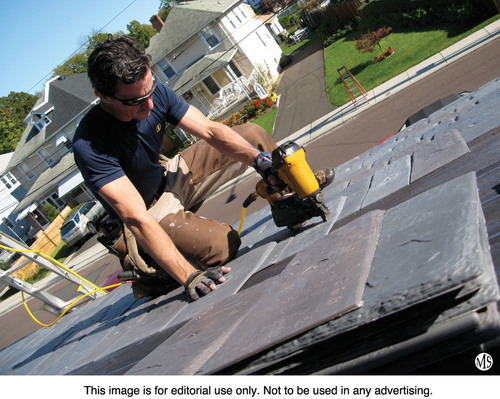 Contractor Mark Clement installs polymer DaVinci Slate tiles on his home.  (PRNewsFoto/DaVinci Roofscapes(R))