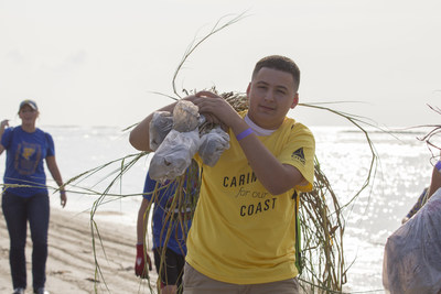 A CITGO volunteer carries some of the 65,000 dune grass plugs planted on Constance Beach, Louisiana