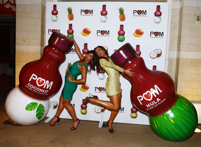 Cheryl Burke and Karina Smirnoff celebrate POM Wonderful's launch of three new 100% Juice Blends by leading 125 people in setting the Guinness World Record for the longest beach-ball bounce in history at the Encore Beach Club at Wynn Las Vegas on August 29, 2013 in Las Vegas.  (PRNewsFoto/POM Wonderful)