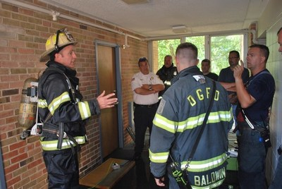 Downers Grove Fire Chief Jim Jackson prepares fire crews for the burn demonstration in the sprinklered and unsprinklered dorm rooms at Midwestern University.