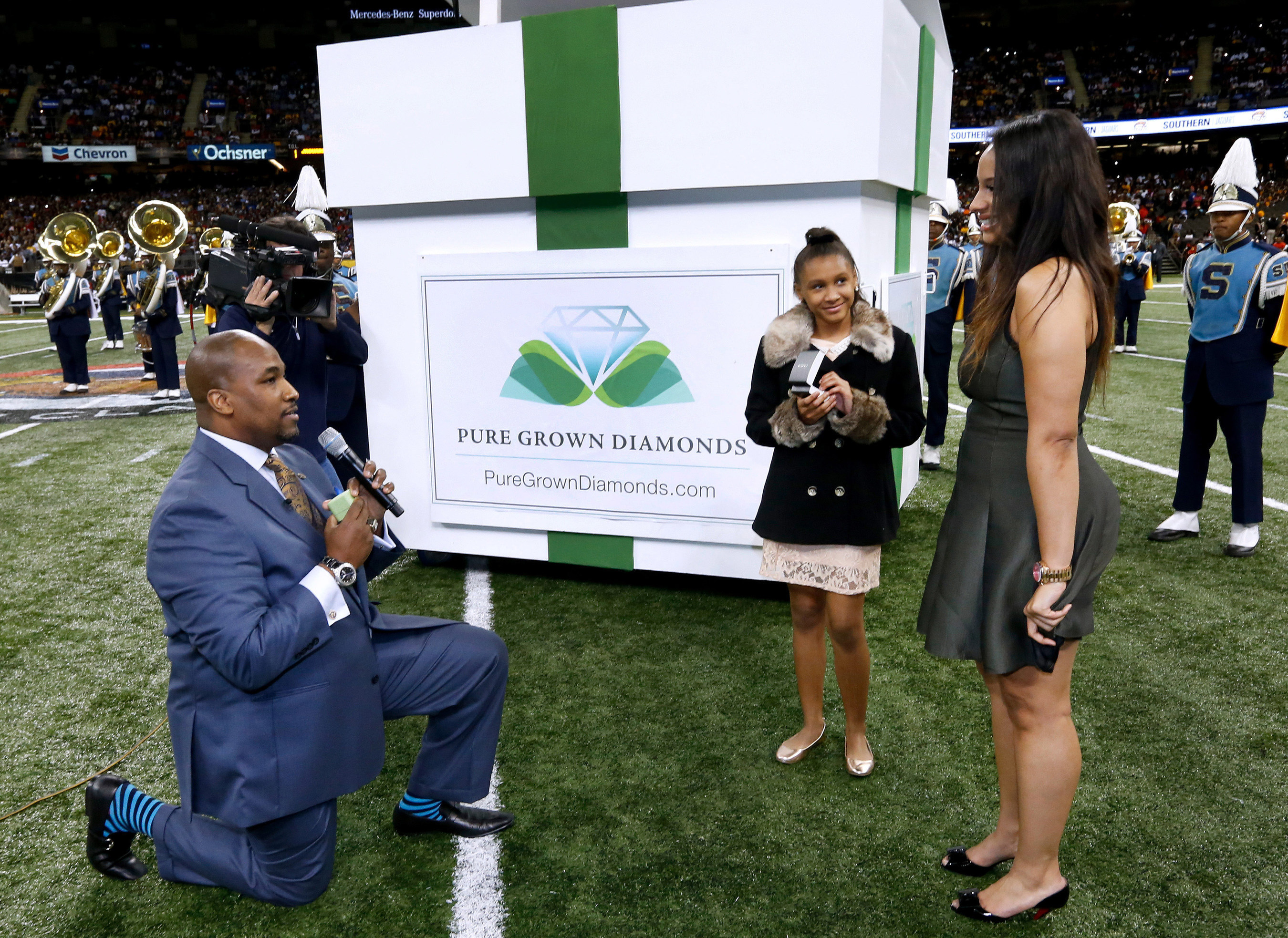 As 12-year-old daughter Ajaya watches mother Brittany Ramsey accept Calvin Mills, Jr.'s proposal with first-of-a-kind lab-created Pure Grown Diamond in New Orleans' Superdome, this weekend. (Jonathan Bachman/AP Images for Pure Grown Diamonds)