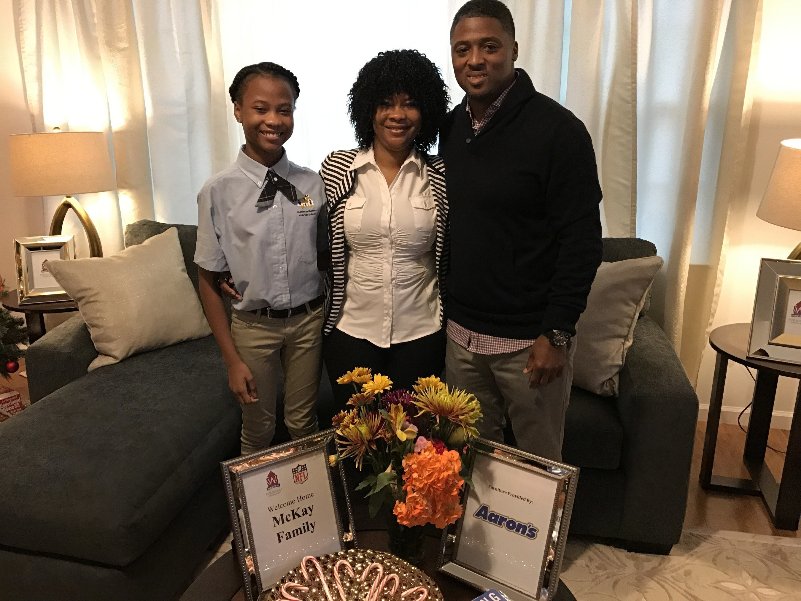 Newark resident Beatrice McKay, a Liberian refugee and mother of two, and former NFL star Warrick Dunn stand with McKay's daughter in the living room of her new fully furnished Habitat for Humanity home.  Aaron's surprised McKay and her family by providing furniture and electronics for her master bedroom, two children's bedrooms, living room and dining room during the 150th Homes for the Holidays (HFTH) home presentation sponsored by Warrick Dunn Charities and Habitat for Humanity Newark.