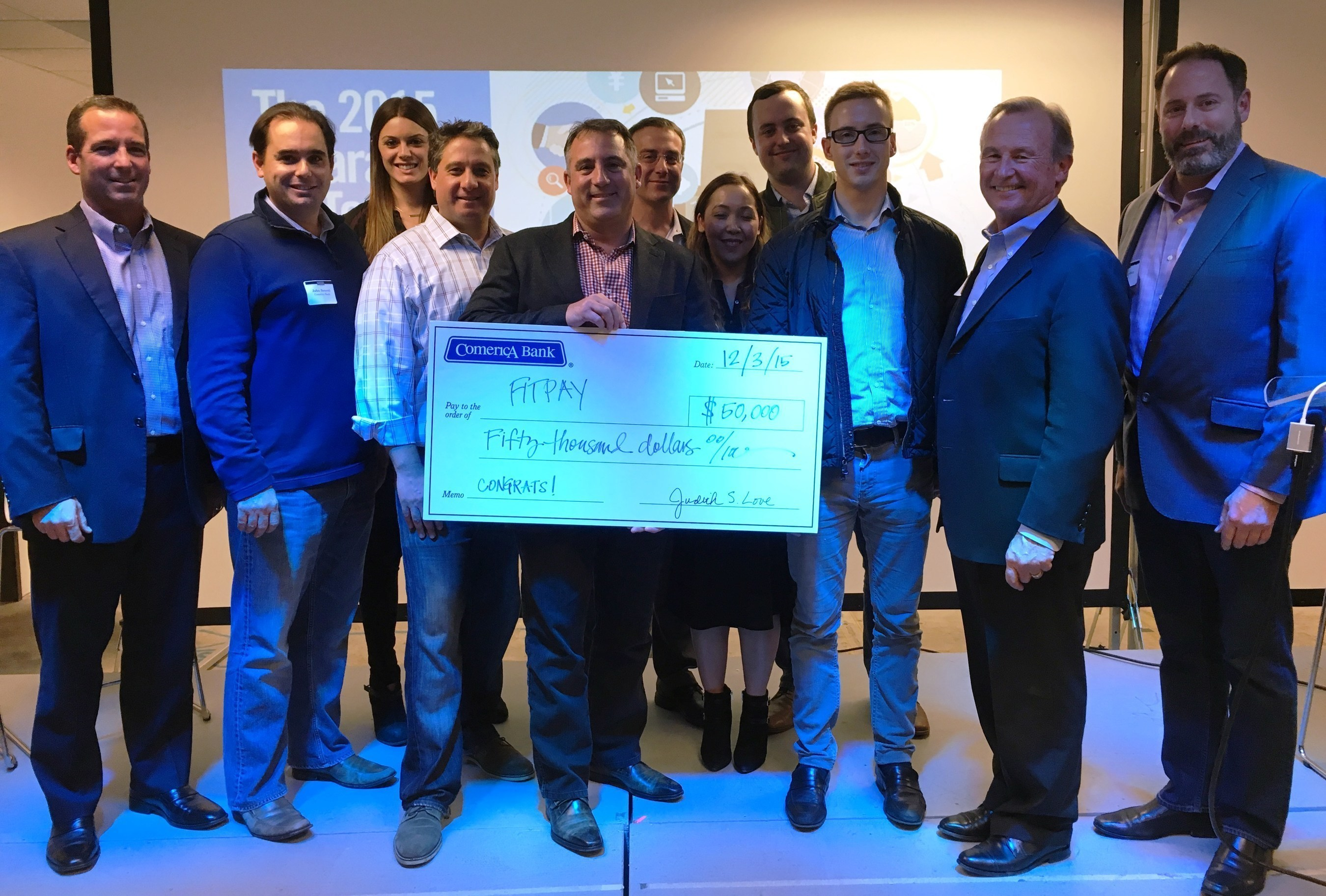FitPay's CEO & Co-Founder Michael Orlando receives a $50,000 check for winning the Comerica RocketSpace Wearable FinTech Challenge.