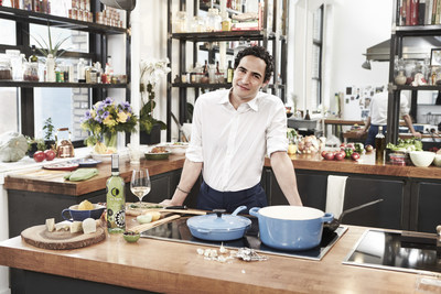 Fashion designer Zac Posen in the kitchen with the Ecco Domani Pinot Grigio bottle he designed. Posen is also a host and home chef who shares his creations on social media using the hashtag #CookingwithZac.