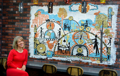 Bruegger's Bagels' $10,000 Artist Challenge winner Taia Morley with her winning design now displayed in Commerce Hill, MN bakery.