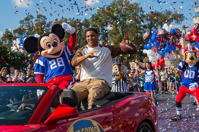 "(FEB. 3, 2014): Super Bowl XLVIII MVP Malcolm Smith rides Feb. 3, 2014 with Mickey Mouse in a parade through the Magic Kingdom at Walt Disney World Resort in Lake Buena Vista, Fla. Smith, a linebacker for the Seattle Seahawks, helped lead his team to a 43-8 victory last night over the Denver Broncos in East Rutherford, N.J. After the game, Smith became the NFL's first defensive player to star in the iconic Disney Parks commercial where he proclaimed ""I'm Going to Disney World!"" (Matt Stroshane, photographer).  (PRNewsFoto/Walt Disney World Resort)"
