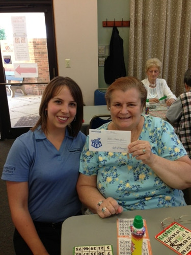 Consumers Energy intern Megan Cary sits with Maryellen Sheppard at the Clinton Township senior center, in Macomb County. Sheppard won a $50 energy gift certificate as interns played bingo with seniors.  (PRNewsFoto/Consumers Energy)