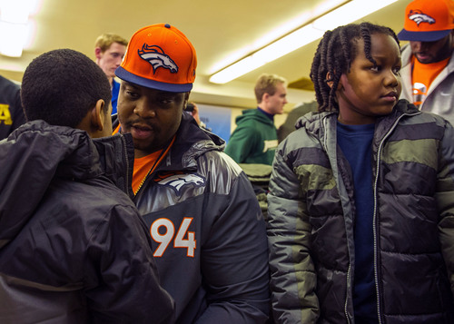 Broncos Defensive Tackle Terrance Knighton from Windsor, Conn. gives a student at Sacred Heart School in Jersey  ...