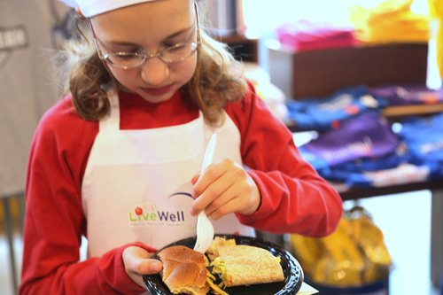 A kid judge taste tests two meals before casting her vote in the National Restaurant Association's Kids LiveWell Recipe Challenge at the McCormick World of Flavors store in Baltimore. (PRNewsFoto/National Restaurant Association)