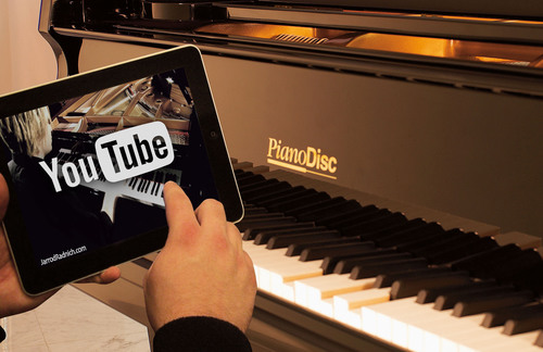 A PianoDisc equipped acoustic piano plays a performance of Jarrod Radnich live on the piano, with perfectly synchronized accompaniment and video, when a YouTube video is played on the innovative new PianoTube LIVE! channel.  (PRNewsFoto/PianoDisc)