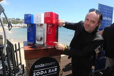 Lars Ulrich from Metallica signs a SodaStream Source at the ribbon cutting event for The American Pavilion at Cannes Film Festival.