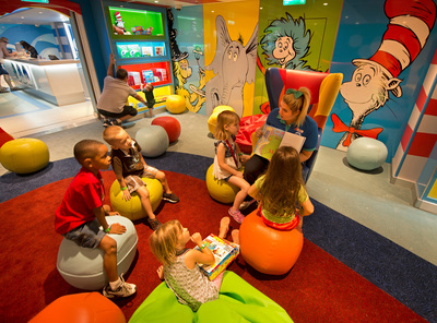 A Camp Ocean counselor reads a Dr. Seuss book to youngsters in the Carnival Freedom's Dr. Seuss Bookville facility -- a unique and dedicated Seuss-themed play space featuring iconic decor, colors, shapes and funky furniture inspired by the whimsical world of Dr. Seuss. (Andy Newman/Carnival Cruise Lines)