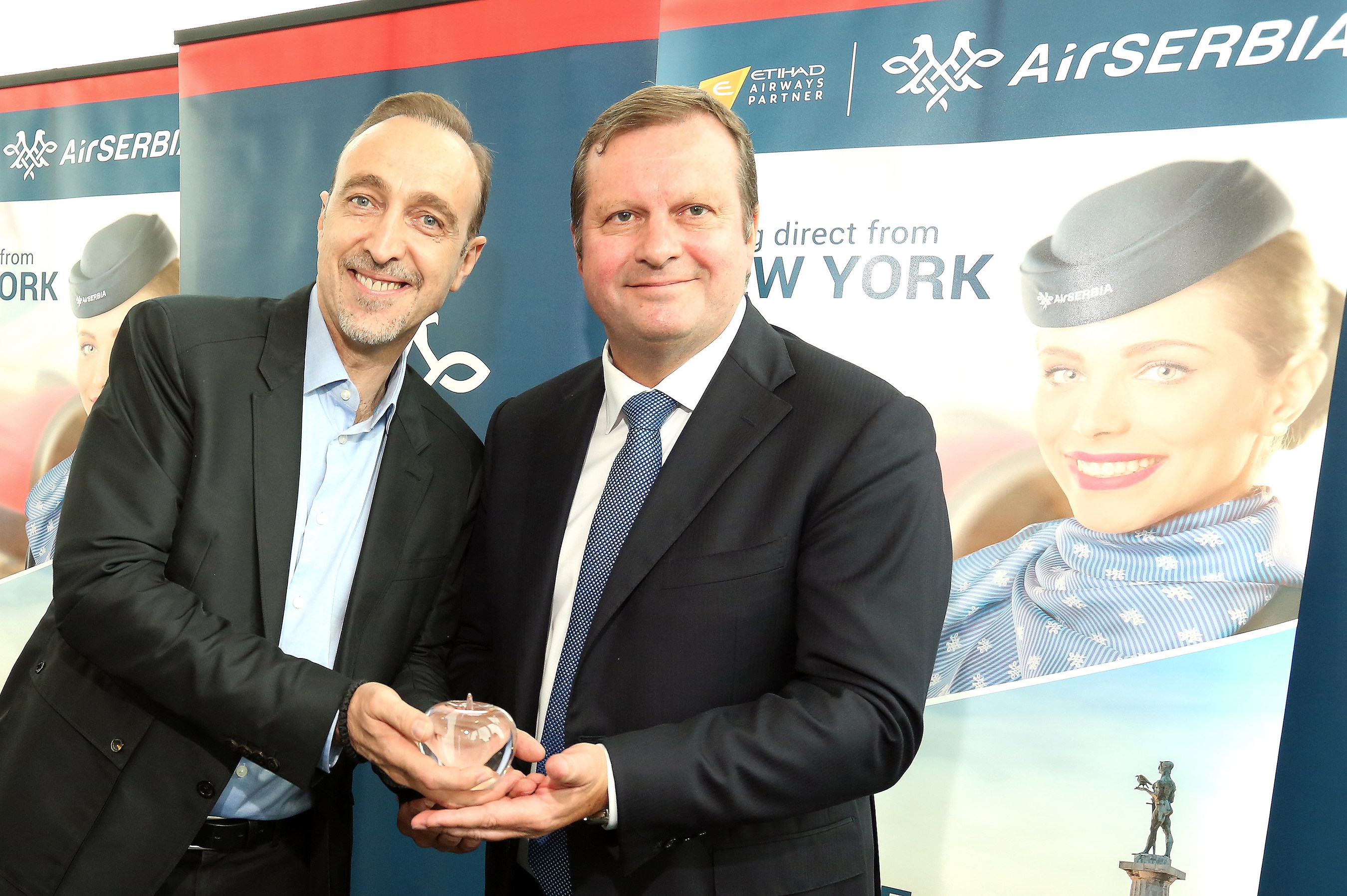 Gert-Jan de Graaf, President and Chief Executive Officer of JFK IAT, LLC presents Dane Kondić, Chief Executive Officer of Air Serbia with a commemorative glass apple to celebrate the start of Air Serbia's non-stop service from Belgrade to New York.