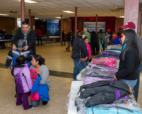 Children - accompanied by their parents - receive free winter coats from the Knights of Columbus at St. Rose Church in New Haven.More than 2000 coats were distributed statewide by the Knights of Columbuson Friday, Nov. 29.  (PRNewsFoto/Knights of Columbus)