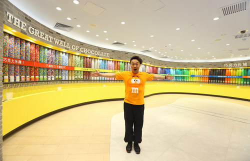 Award-winning singer-songwriter Eason Chan celebrates the official opening of M&M'S World(R) Shanghai - Asia's first M&M'S World(R) store - at the Great Wall of Chocolate, which features 132 tubes of M&M'S(R) Chocolate Candies. M&M'S World(R) Shanghai is the fifth flagship store in the world and officially opened August 8, 2014, on the popular East Nanjing Road in Shanghai. (PRNewsFoto/Mars Retail Group)