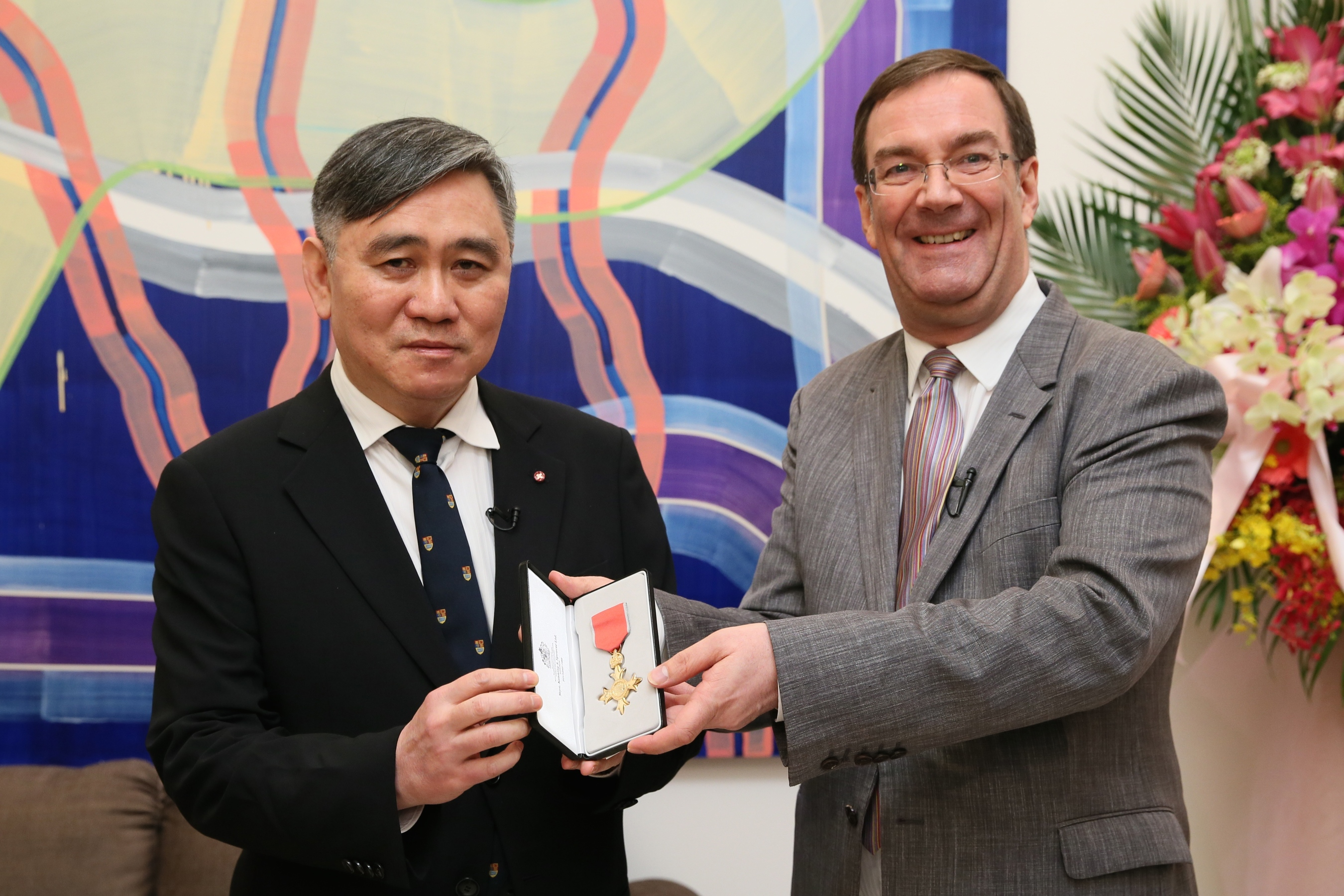 British Representative Chris Wood presents Dr. Winston Wong, OBE with the official insignia