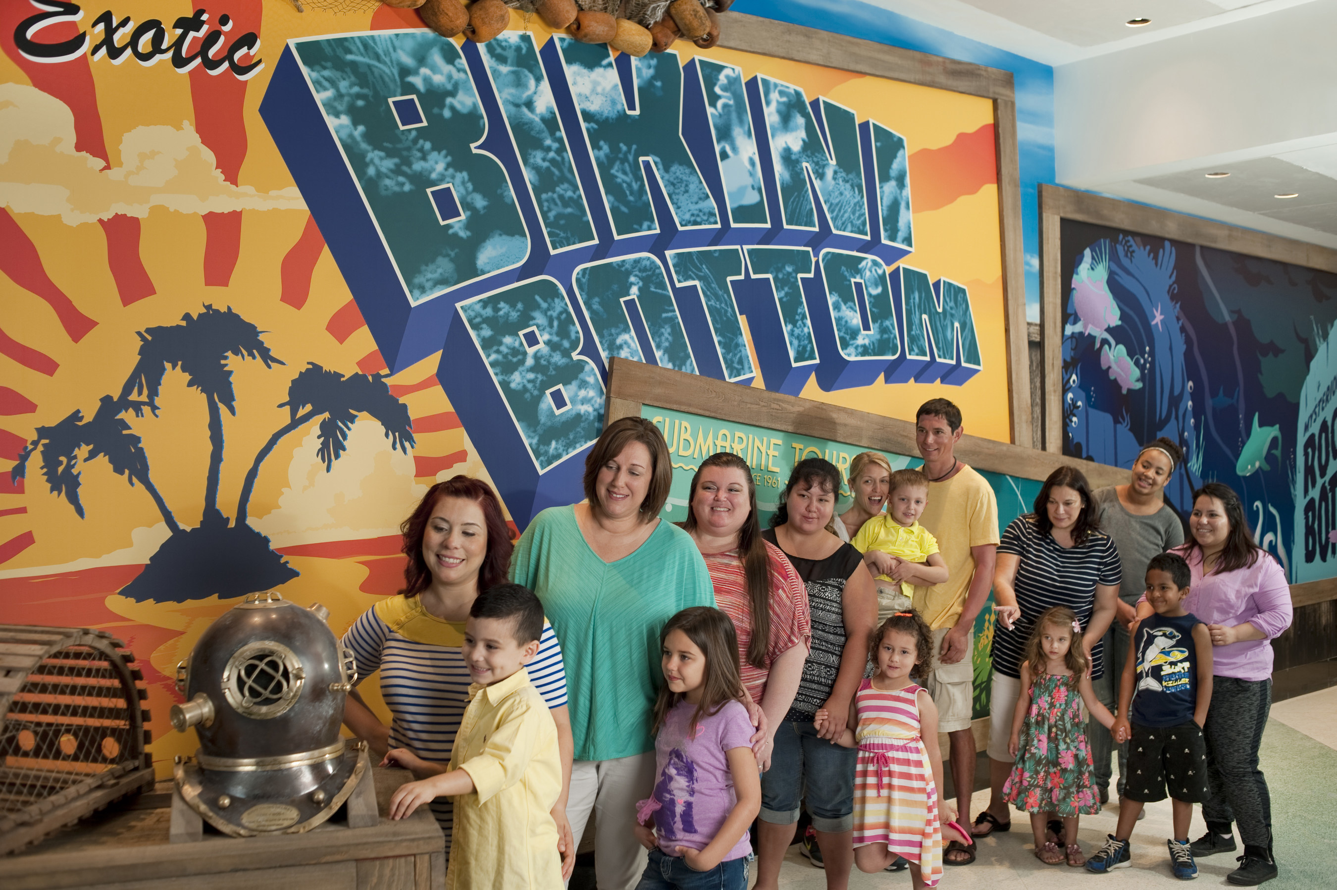 Children and parents view a brass dive helmet and crab trap near the Bikini Bottom mural before entering the ...