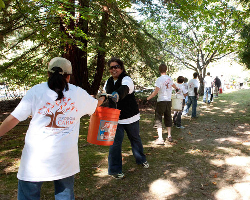 Expedia Day of Caring - A long line of Expedia employees clean up a Seattle-area park.  (PRNewsFoto/Expedia, ...