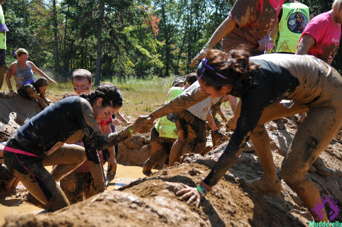 Mudderellas show teamwork is essential to completing the course at the inaugural Mudderella 2013 event in ...