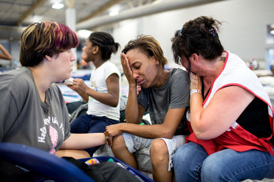 Courtney Robinson (center) is nearly certain that her home is destroyed because of the record flooding in Louisiana. She is staying at a Red Cross shelter with her five children and husband who fled the flood waters with some food and water and a change of clothes for the family. She shared their story with Red Cross relief worker Elizabeth Stander, and Rachel Ambeau, who is also displaced and staying at the Red Cross shelter, in Gonzales, Louisiana. Red Cross Photo by Marko Kokic