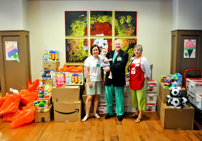 Dr. Labron Chambers (second from right), pediatric anesthesiologist, posing with his wife Carroll Chambers (left), son Tripp (second from left), and Ronald McDonald volunteer Anita Pangle (right) in front of the toys and supplies donated by Southeast Anesthesiology at the Ronald McDonald House.  (PRNewsFoto/Southeast Anesthesiology Consultants)