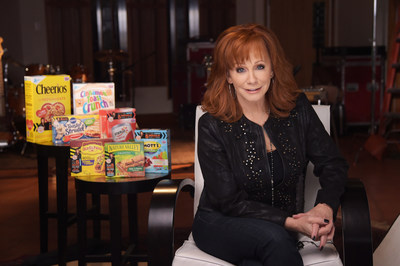 """Superstar entertainer Reba shoots a public service announcement for Outnumber Hunger, a campaign from General Mills, Big Machine Label Group and Feeding America aimed at raising awareness of the one in six people struggling with hunger in America. She will kick off the campaign's fourth year with a special concert event, """"Reba and Friends Outnumber Hunger,"""" beginning April 17 and will be featured on more than 60 million General Mills packages, including Cheerios."""