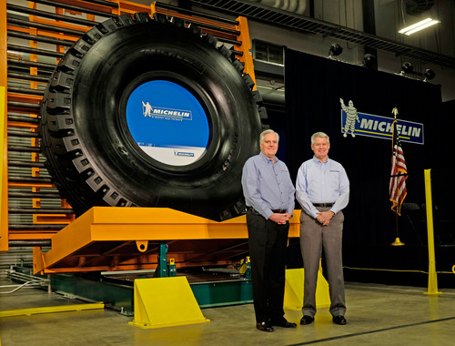 Michelin North America chairman and president, Pete Selleck, and Bruce Brackett, senior vice president, Michelin Earthmover & Industrial Tires Worldwide stand in front of the first tire from Michelin's newest manufacturing facility in South Carolina.  (PRNewsFoto/Michelin)