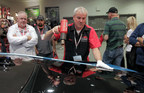 Attendees of 2015 SEMA look on as Mike Powell, Eastman Tech Services, demonstrates the heat shrinking installation method for LLumar window tint on a West Coast Customs car.