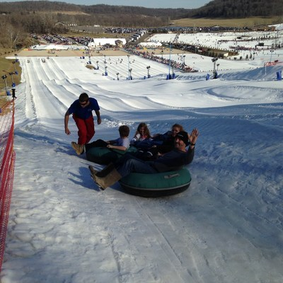 An injured service member and his family prepare to snow tube down the slope.