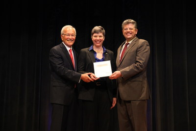 Jennifer Shasky Calvery (center), spouse of Pentagon Force Protection Agency Director Steven E. Calvery (left), is presented with a certificate of appreciation for her support and faithful service by Michael L. Rhodes (right), director of administration for the Office of the Secretary of Defense, who presided over the ceremony.