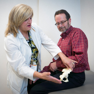 Certified nurse practitioner Anne Lake, the coordinator of Wake Forest Baptist Medical Center's Fracture Liaison Service, uses a bone model to make a point to patient Ed Eklund of Winston-Salem, N.C. Credit: Cameron Dennis / Wake Forest Baptist HealthWire. (PRNewsFoto/Wake Forest Baptist HealthWire)