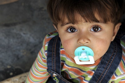 Narien*, 2 and a half years old, sits on the floor of her family's tent in a camp for displaced people on the northern Syrian border--Save the Children is helping families facing and fleeing the Syrian conflict eat, learn, and stay safe. Photo credit: Ahmad Baroudi/Save the Children