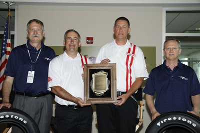 Jim Bailey, BorgWarner (far left), and Steve Holman, Indiana Section of SAE International (far right), presented engineers Dale Harrigle and Brett Schilling (center left and right) from Bridgestone Americas Motorsports with the 2013 BorgWarner Louis Schwitzer Award for the Firestone Firehawk(TM) Indy 500 Race Tire. Product photo courtesy of Firestone. IndyCar (and Design) are registered trademarks of Brickyard Trademarks, Inc., used with permission. IZOD is registered trademark of pVH Corp, used with permission.  (PRNewsFoto/BorgWarner Inc.)
