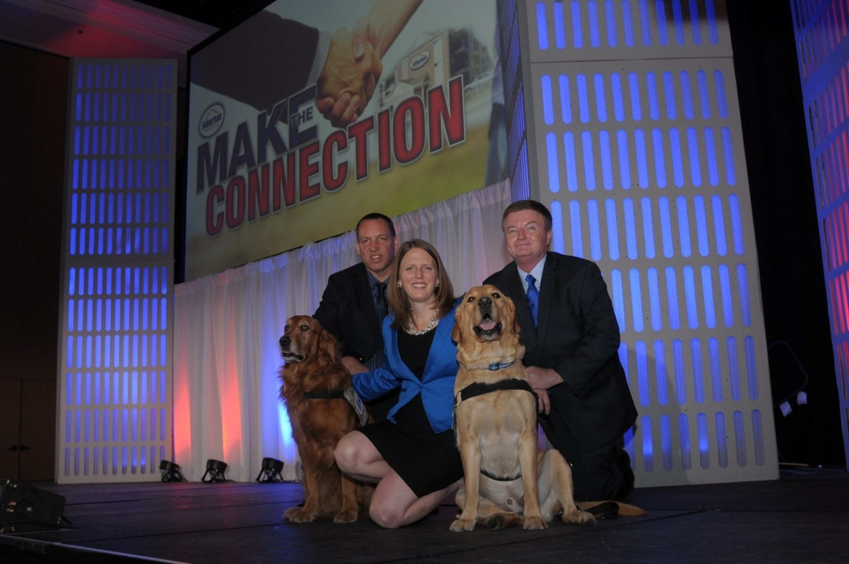 Choice Hotels' Suburban Extended Stay brand partners with America's bravest by supporting Maryland-based Warrior Canine Connection  Pictured: (Humans) Rick Yount, founder and executive director of Warrior Canine Connection Caragh McLaughlin,  head of brand management for Suburban Extended Stay, Choice Hotels International Bill Petschonek, director of brand strategy for Suburban Extended Stay, Choice Hotels International  (Canines) Huff (left) Ron (right) (PRNewsFoto/Choice Hotels International, Inc)