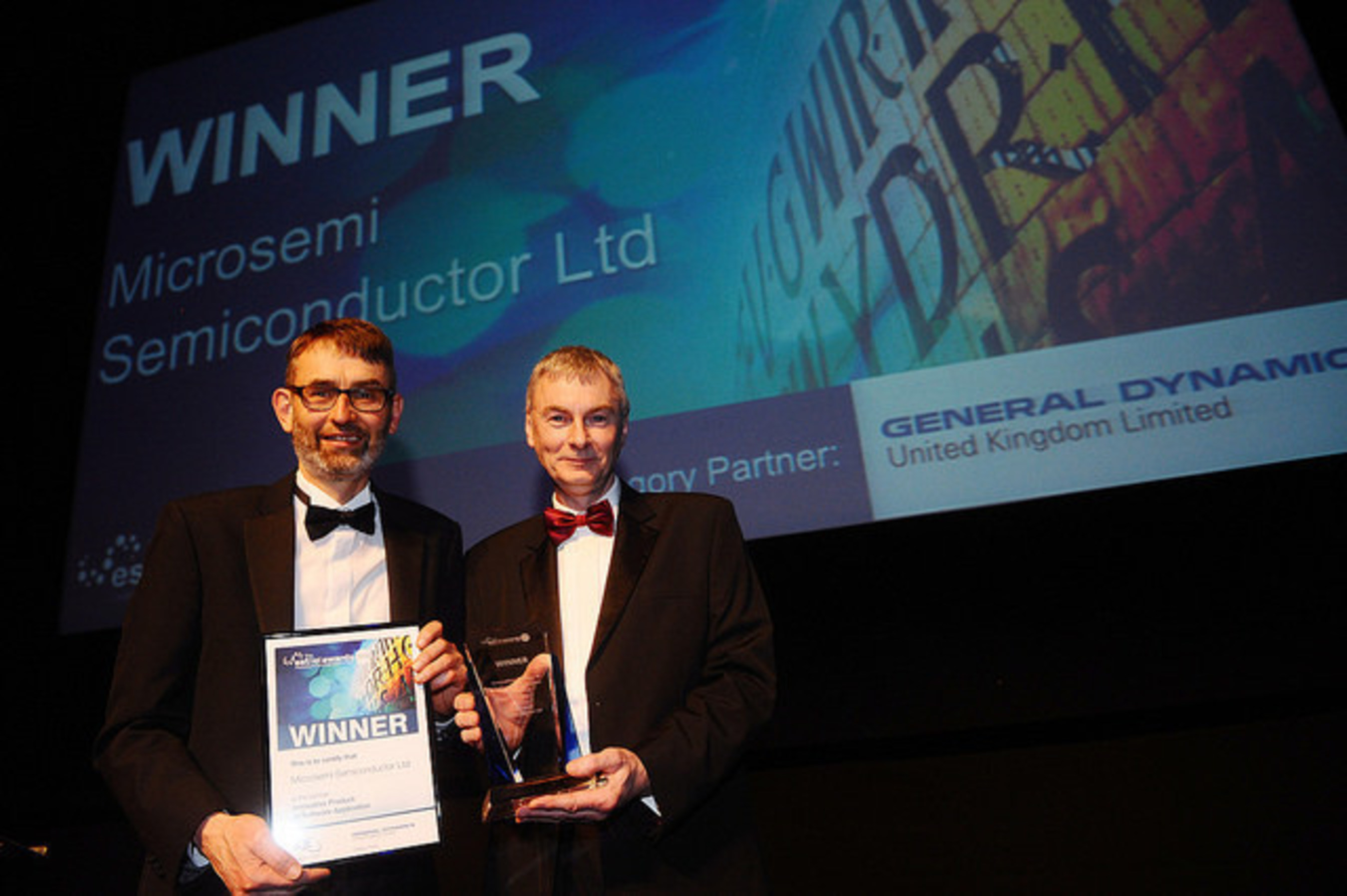 Piers Tremlett (left), senior engineer at Microsemi, accepted the Innovative Product or Software Application Award from Rob Rolley of General Dynamics (right) during the ESTnet Award ceremony in Wales