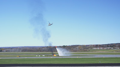 The unmanned K-MAX drops water on a fire during a demonstration at Griffiss International Airport in Rome, New York. The Indago quadrotor identified hot spots and relayed that information to an operator who directed the K-MAX to autonomously retrieve water from a nearby pond and drop it onto the fire. Photo courtesy Lockheed Martin.