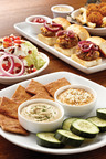 Mimi's Cafe introduces new Small Plates menu, tapas-style dishes made for sharing. Selections include Mimi's signature Hummus Sampler, original and sundried tomato hummus with basil and feta, served with baked whole wheat flatbread chips and cucumbers.  (PRNewsFoto/Mimi's Cafe)