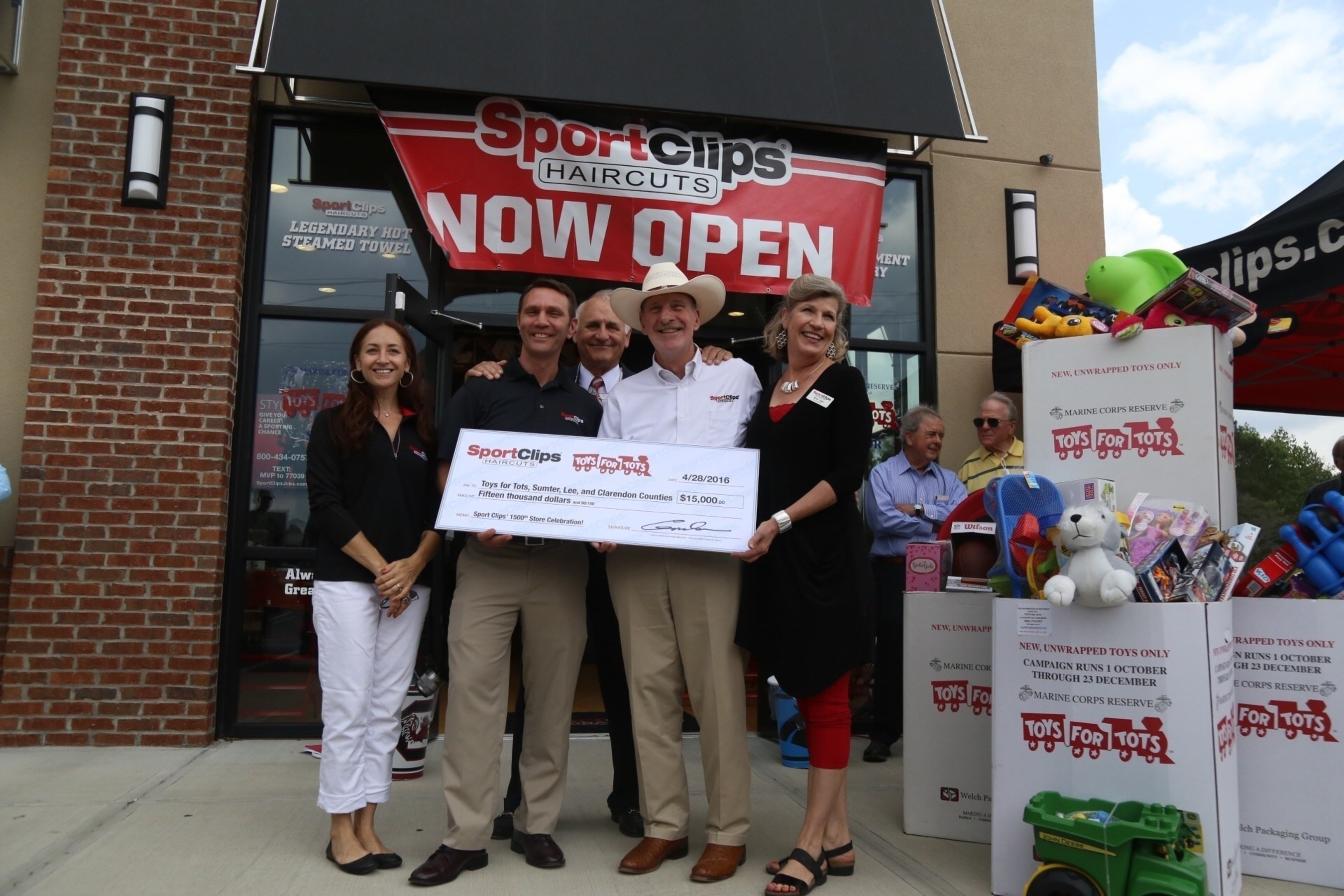 Sport Clips Haircuts celebrates 1,500th store milestone in founder's hometown by giving back to area youth. Front row (l to r) Sharon and Zach Payer, Sumter Sport Clips Haircuts franchisees; Sport Clips Haircuts Founder and CEO Gordon Logan and wife Bettye; back row Harvey Senter, Toys for Tots regional coordinator.