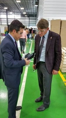 Antonio Ibanez, COO of Ficosa North America, shows TNECD Commissioner Randy Boyd a rearview mirror produced in the new Ficosa plant.