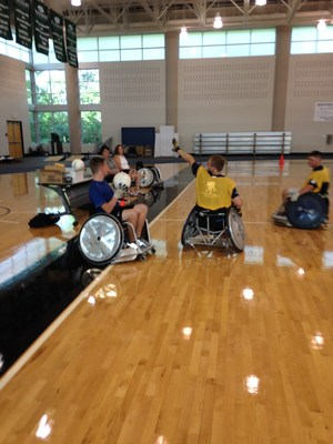 WWP veterans, family members, and caregivers play wheelchair rugby at a weekend adaptive sports camp at the Lakeshore Foundation.