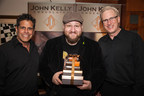 "A happy Stephen Glickman (""Big Time Rush"") embraces a Tower of John Kelly Chocolates with John Kelson and Kelly Green, owners of the company."
