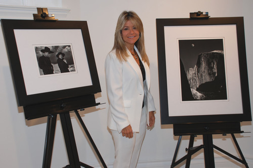"The College of New Rochelle President Judith Huntington with two of the Ansel Adams photos from the Museum Set. Photos shown, from left, ""Georgia O'Keeffe and Orville Cox, Canyon de Chelly National Monument, Arizona, 1937"" and ""Moon and Half Dome, Yosemite National Park, California, 1960.""  (PRNewsFoto/The College of New Rochelle)"