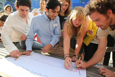 "Students and graduates discuss a business plan that helps tackle climate change at Imperial College London, UK. Participants in the 2015 edition of Climate-KIC's European ""The Journey"" summer school programme work on ideas for solutions to real-world climate change related issues, and compete in teams. Based on their own creativity and climate knowledge, the teams present a detailed business plan to a judging panel consisting of leading European venture capitalists, startup entrepreneurs and scientists."