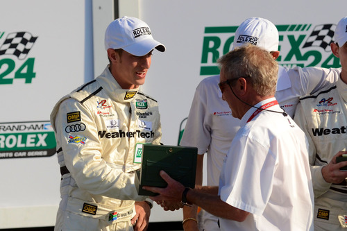PR Newswire-supported racer Dion von Moltke receives his winning Rolex from race legend Hurley Haywood. ...