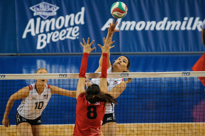 USA's #6 Tori Dixon is hitting against a Canadian blocker in the first match of the NORCECA Olympic Qualification Tournament, the first public display of the partnership connection between USA Volleyball and Blue Diamond Almond Breeze.