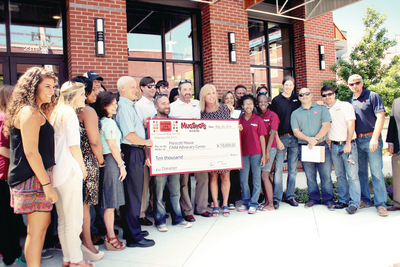 This photo released by Mugshots Grill & Bar shows the presentation of a $10,000 check to the Prescott House Child Advocacy Center as a result of a fundraising event at the restaurant. (PRNewsFoto/Mugshots Grill & Bar)