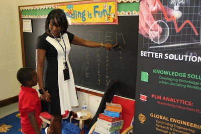 Alisa Harewood, head of the office of the CEO at Tata Technologies, teaches the meaning of STEM (science, technology, engineering and math) to a young student at Clark Preparatory Academy in Detroit, Mich. (PRNewsFoto/Tata Technologies)